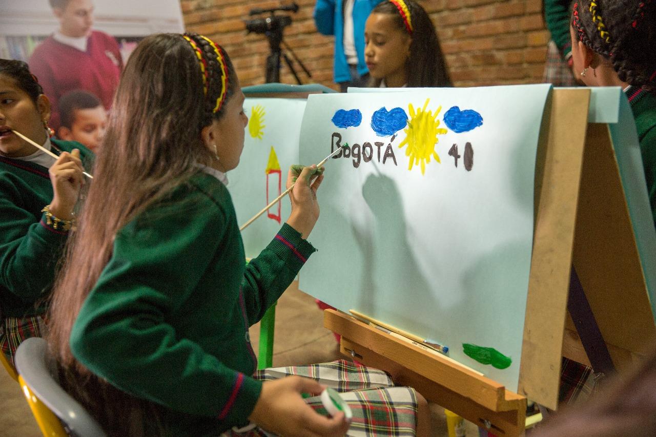Niña pintando a Bogotá