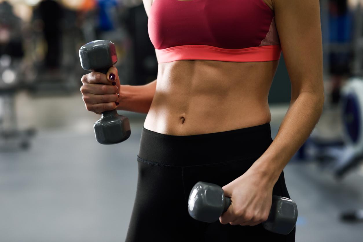 Una mujer trabajando su tono muscular en el gimnasio
