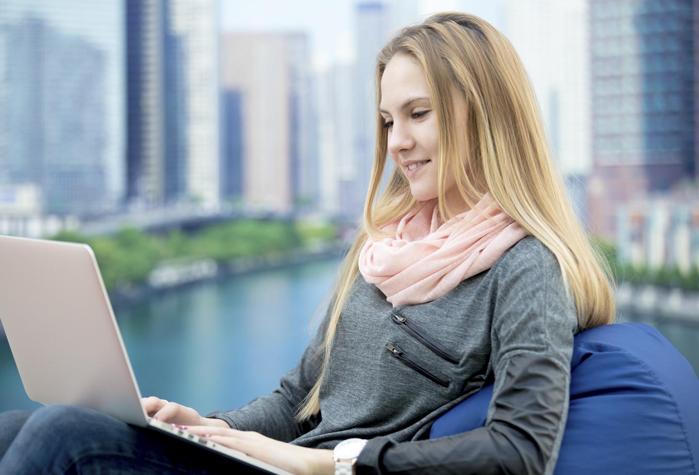 Una joven asiste una clase virtual en el exterior