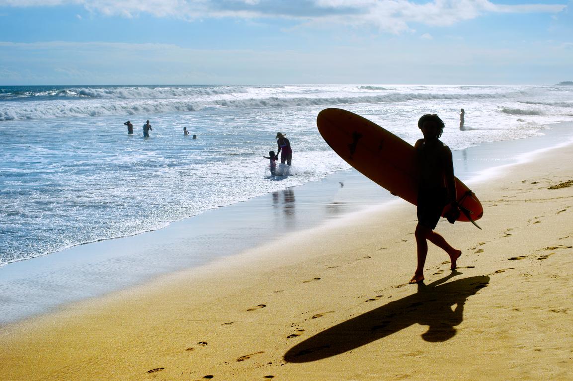 Un joven practicando surf en sus vacaciones