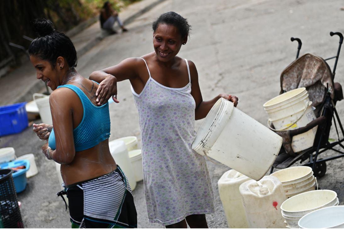 Dos mujeres se bañan en una calle de Caracas.
