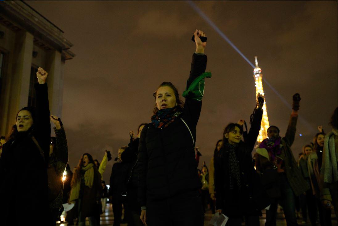 """Mujeres levantan los puños mientras participan en el performance """"Un violador en tu camino"""""""