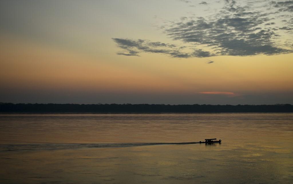 Se ve un barco navegando por el río Amazonas al atardecer.