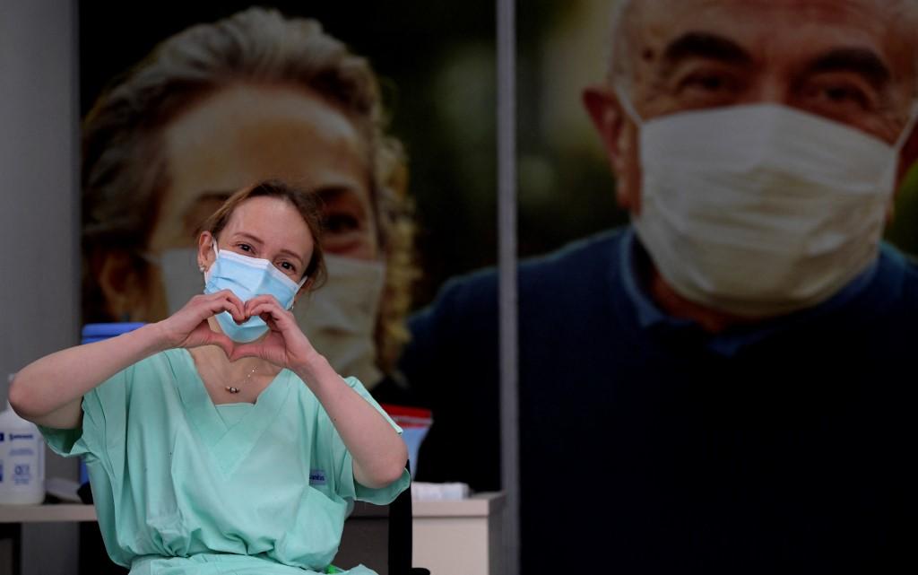La doctora Silvia Gelvez hace gestos tras recibir una dosis de la vacuna Pfizer