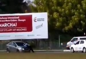 El guarda de tránsito intenta sostenerse en la tapa del carro.