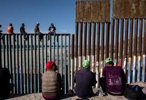 Migrantes centroamericanos en el muro con Estados Unidos