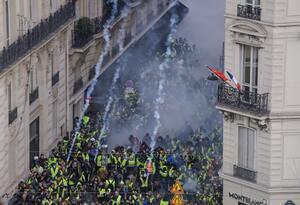 """""""Chalecos amarillos"""" gritan """"Macron dimisión"""", en medio de disparos de gases lacrimógenos cerca de la Avenida de los Campos Elíseos."""