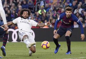 Marcelo y Piqué disputan un balón en un clásico español