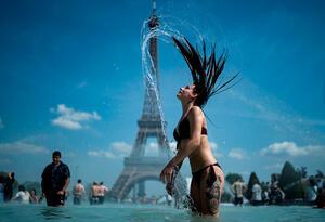 Una mujer se refresca en la fuente de la Plaza del Trocadero, en París, este 25 de junio de 2019, con la Torre Eiffel en el fondo