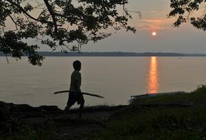 Un niño indígena colombiano camina a orillas del río Amazonas.