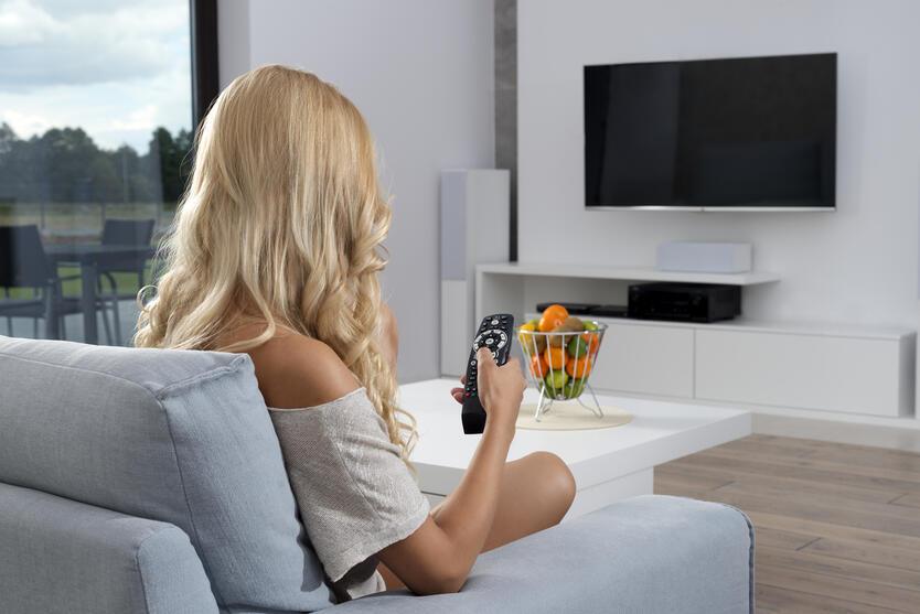 Una mujer descansa en su sala frente al televisor