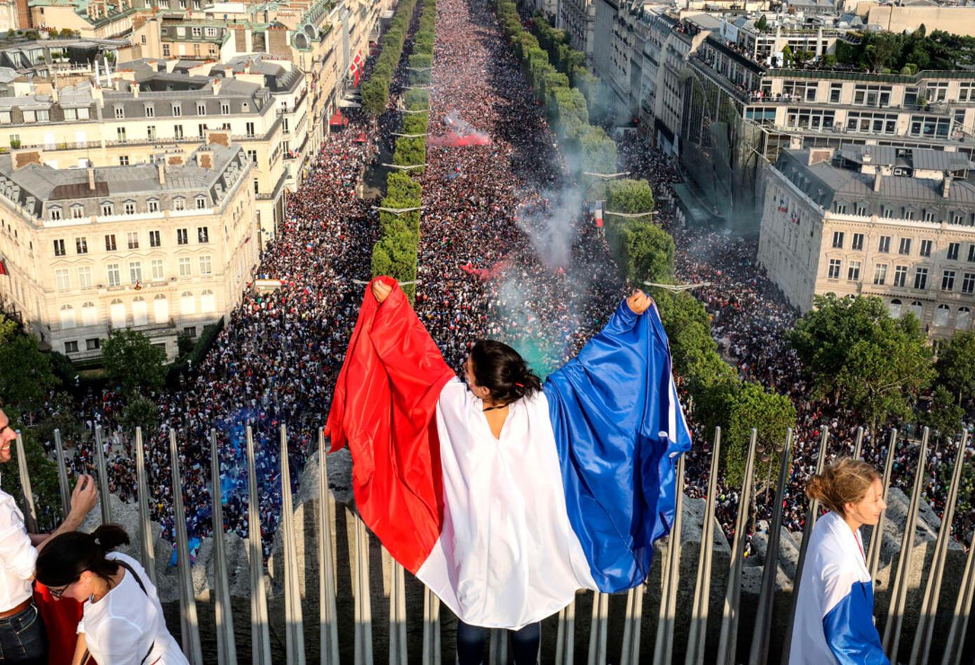 Una hincha de Francia exhibe la bandera por las calles de París