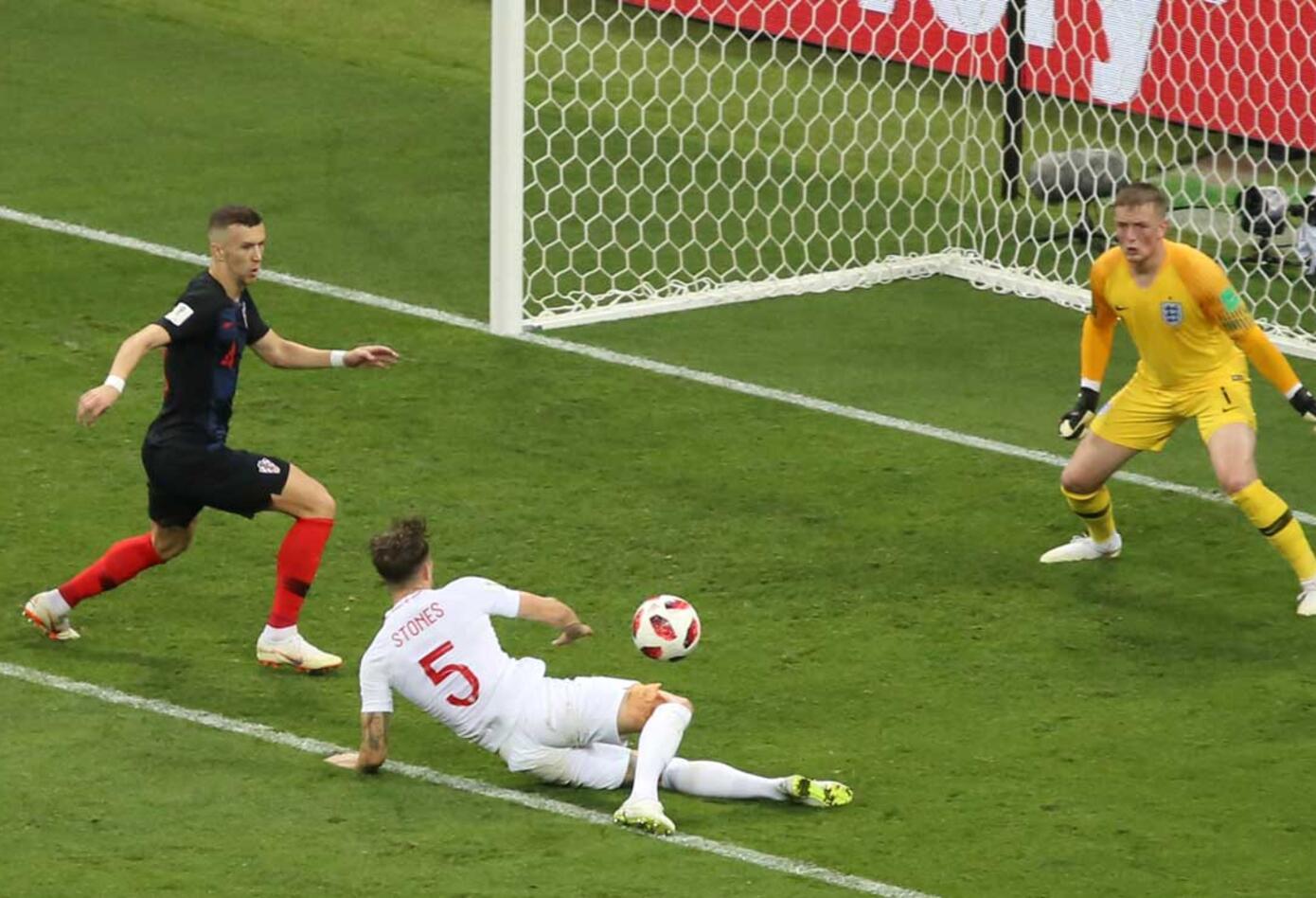 John Stones intenta rechazar un balón ante la presión de Ivan Perisic