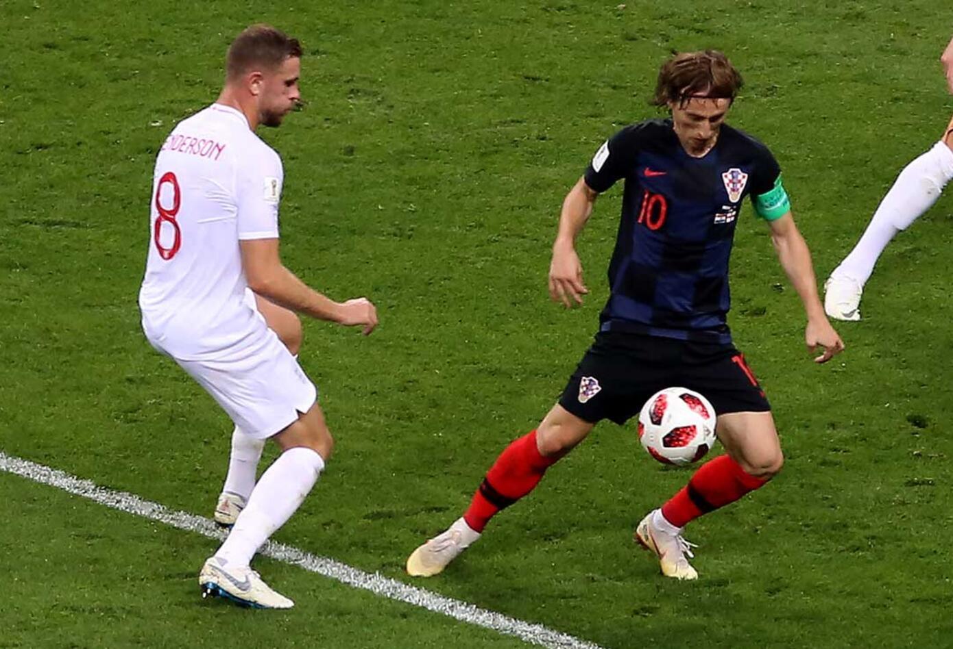 Luca Modric maneja la pelota ante la mirada de Ante Rebic