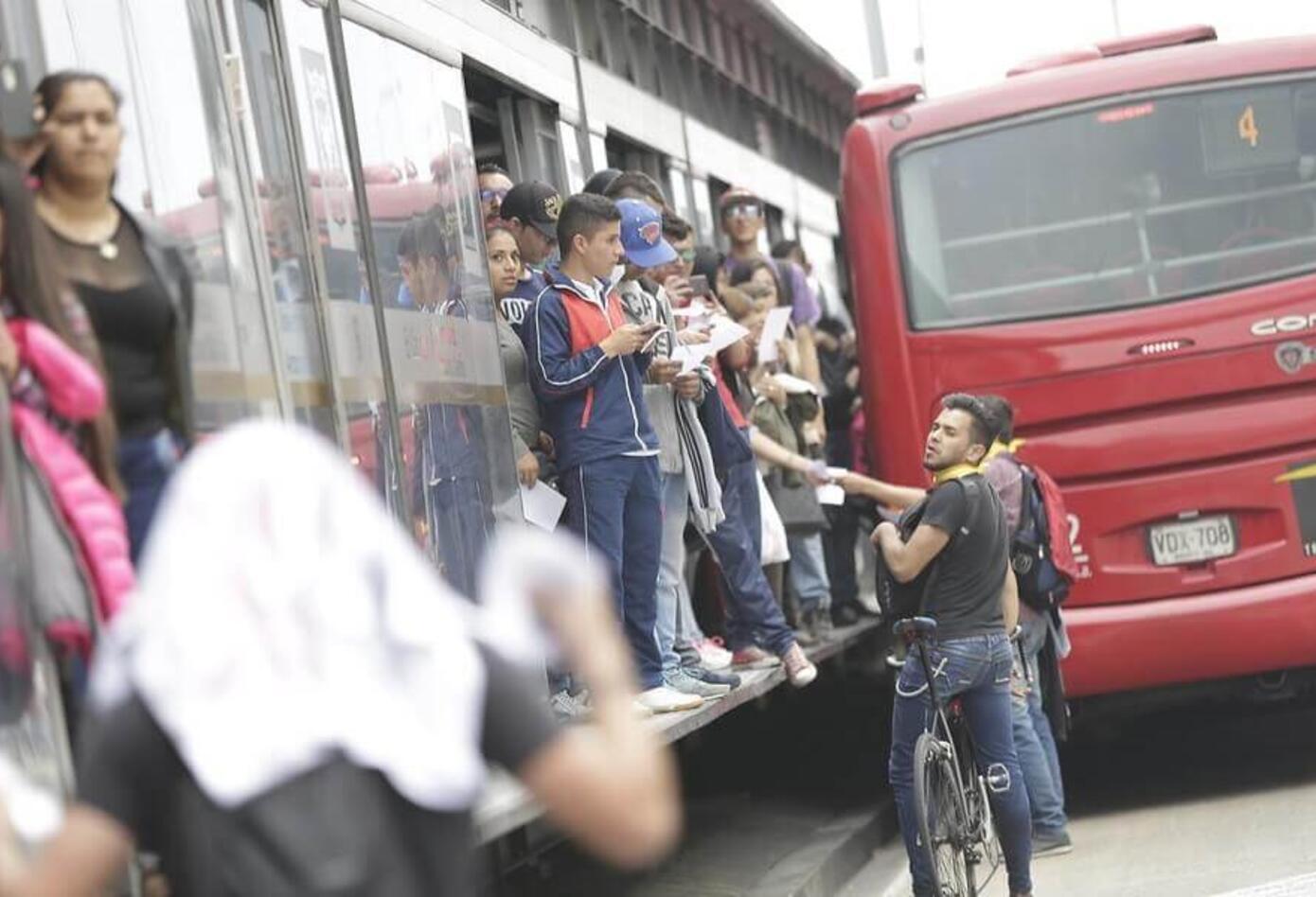 Estudiantes a paso por una de las estaciones de Transmilenio saludan a los usuarios de los articulados