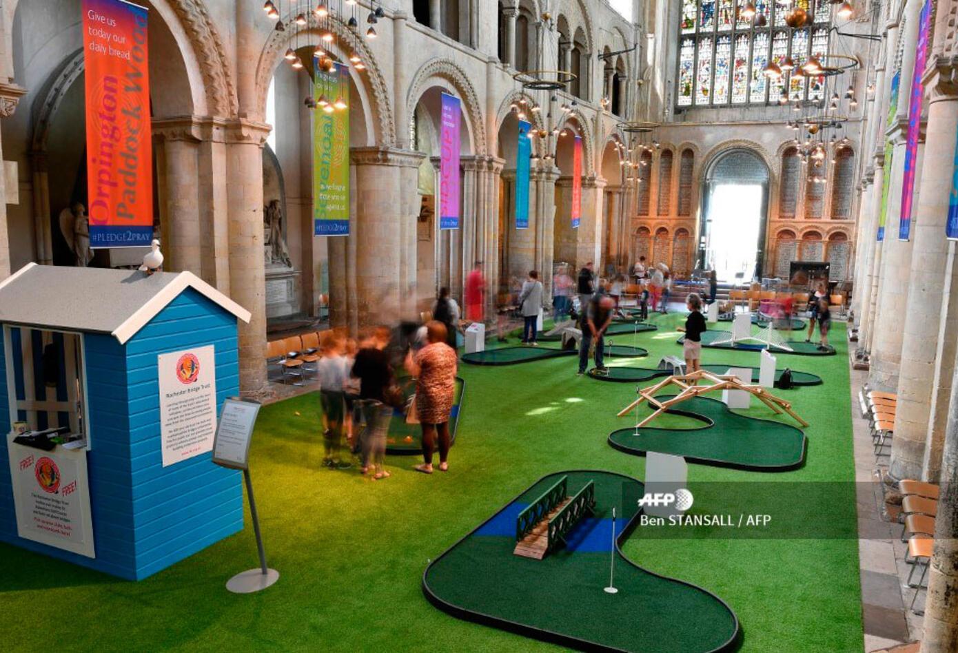 A donde normalmente se encuentran hileras de bancos, se ha desplegado una gran moqueta verde, de césped sintético, donde los clubes de golf acogen a los parroquianos.