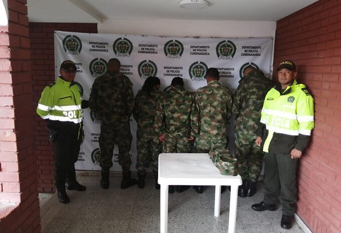 Cuatro hombres y una mujer vestidos con uniformes militares.