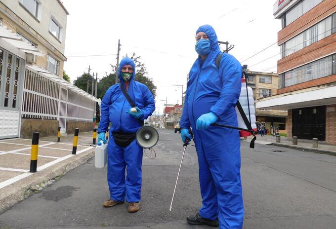 Fernando y Alberto desinfectan casas y carros en Bogotá.