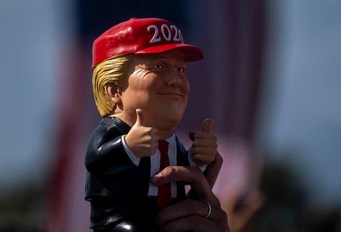 Seguidor de Donald Trump sostiene un muñeco de presidente en un evento en Tampa, Florida