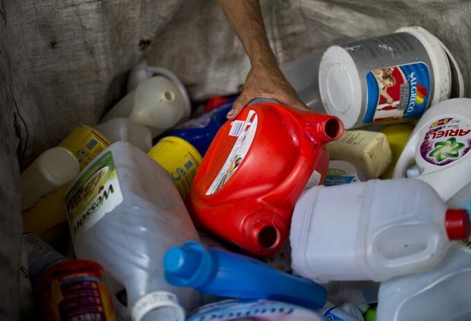Hombre recolecta botellas de plástico en un depósito de reciclaje en Cali.
