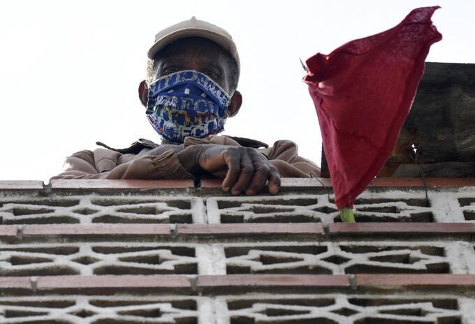 Coronavirus en Colombia - Hombre exhibe trapo rojo frente para exigir ayuda al gobierno.