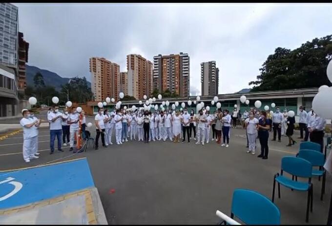 Los compañeros elevaron globos blancos para despedir al auxiliar de enfermería.