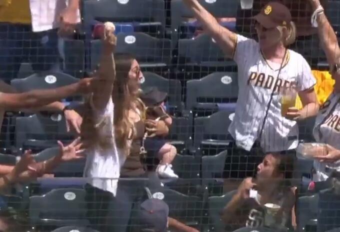 Mujer con bebé en brazos logró atrapar una pelota